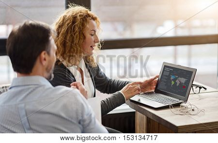 International business. Side view of involved ginger woman presenting information to from laptop man sitting against big window.
