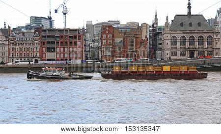 LONDON UNITED KINGDOM - NOVEMBER 20: Barges Towed by a Tugboat on the River Thames in London on NOVEMBER 20 2013. Transporting Waste by Water in Sealed Containers on Barges Which are Pulled by Tug in London United Kingdom.