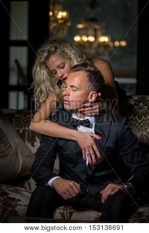 Fancy woman seducing man in black suit