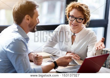 Acute contradictions. Smiling middle-aged man and woman having discussion pointing at laptop while sitting against big window.