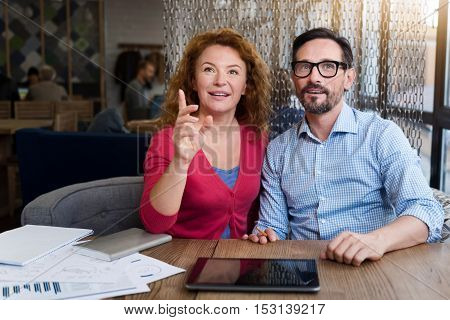 Look how beautiful. Ginger woman sitting at table, looking forward and pointing with her hand.