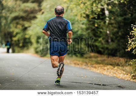 active elderly man running down road in autumn Park