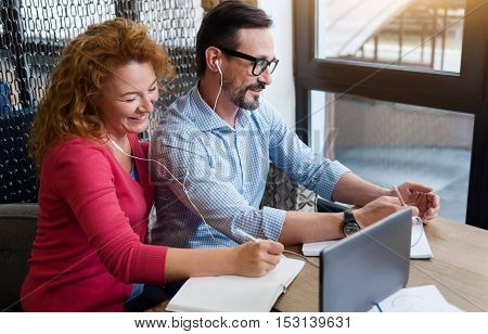 Never late to study. Side view of middle-aged couple taking notes while getting information from tablet through earphones.