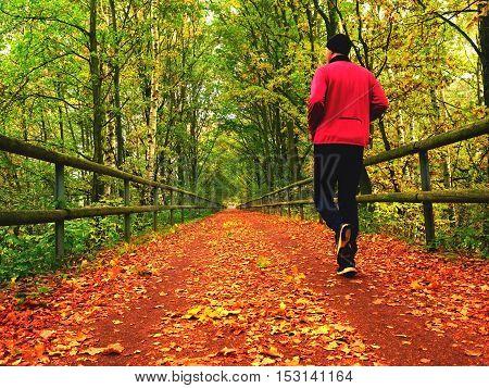 Sportsman In Pink And Black Sportswear Run On Road. The Man Slowly Run
