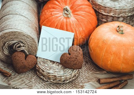 Autumn or thanksgiving greeting blank place card with copy space. Still life with orange pumpkins, gingerbread hearts sweet cookies, brown candle, twine on table craft background. Fall holliday harvest concept.