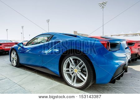 ABU DHABI, UAE - OCTOBER 08, 2016: A shiny blue Ferrari parked outside the Viceroy Hotel in Abu Dhabi which is known for its hosting of Formula One Grand Prix races