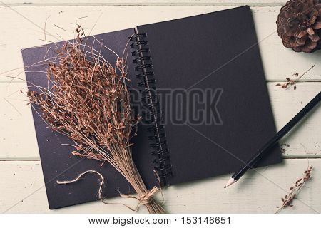 blank notebook and flower on old wooden table Vintage tone
