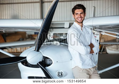 Cheerful young man in white shirt standing with arms crossed near the airplane