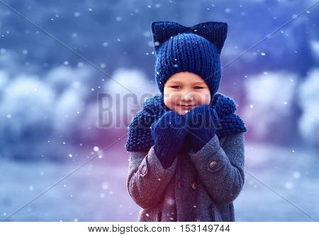 Cute Kid In Knitted Wear And Felted Coat Under Winter Snow
