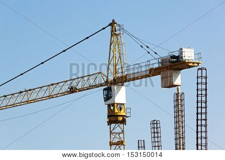 High rise crane against blue sky operating at construction site