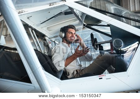 Happy young man pilot sitting in small plane and talking using headset