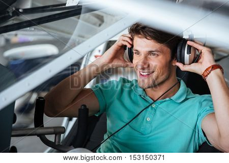 Happy handsome young man pilot sitting in cabin of small plane