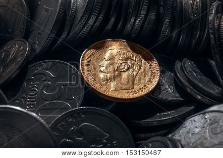 coin from precious metal of gold against the background of coins of small advantage from cheap metals.