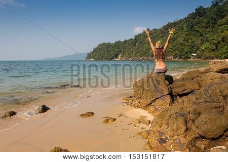 Girl sitting on coastal sea rocks. Well being healthy lifestyle.
