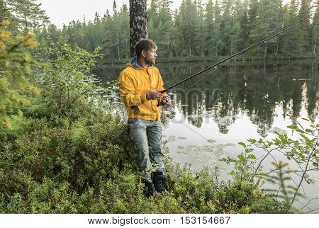 Man is fishing on the shore of beautiful forest lake