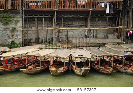 Chinese tourists boats docked along a bank of the Tuo Jiang River in the village of Fenghuang China in Hunan province.