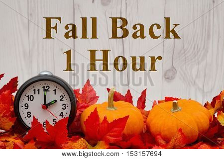 Daylight Savings Time message Some fall leaves and retro alarm clock and pumpkin on weathered wood with text Fall Back 1 Hour