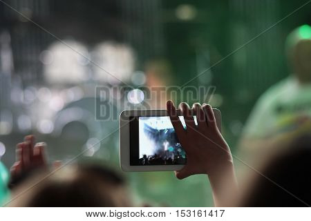 the person subscribing concert of the famous band using a mobile phone