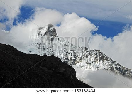 Huandoy mountain peak with clouds in the peruvian Cordillera Blanca