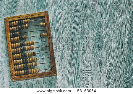 Old wooden scratched vintage decimal abacus on a blue wooden board for the background. Top view. Flat lay. Crop. The style of the old scratched photo with noise
