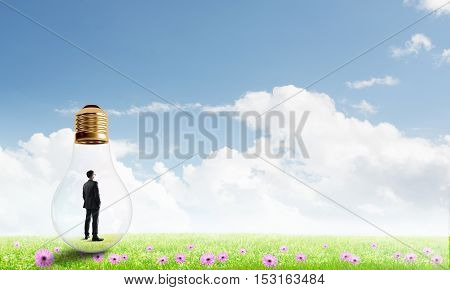 Businessman inside glass light bulb outdoors looking away