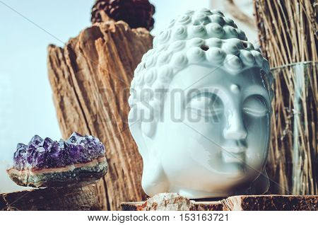 White head of Buddha with purple amethyst stone on wooden background. Buddhism religion concept. Esoteric, yoga, meditation, spiritual enlightenment.