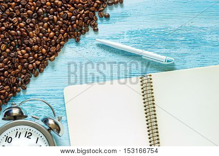 Single simple empty white notebook with a blank for drawing or writing white plasic pen scattered roasted coffee beans and alarm clock with silver metal bells are on a Desktop from blue wooden plank. Top view. Mock up. Flat lay