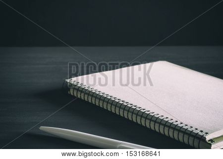 Single simple empty white notebook with a blank for drawing or writing and white plastic pen are on a Desktop from black chalkboard. Mockup. Toned and grained