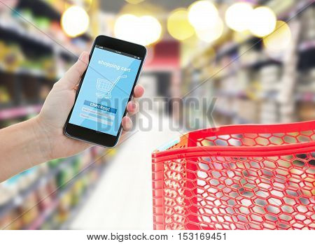 hands holding mobile smart phone with mobile shop, comercial center with red cart in background