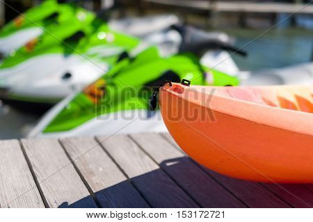Bright orange canoe in front of some jet skis on a dock in Florida