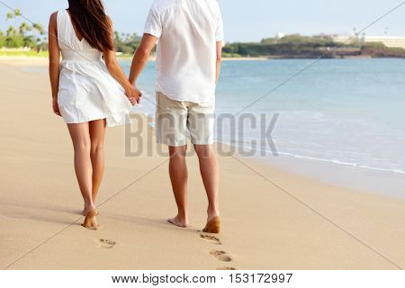 Honeymoon barefoot couple holding hands walking on romantic beach vacation holidays leaving footprints in the golden sand with feet. Young people from behind in white shorts and dress beachwear.