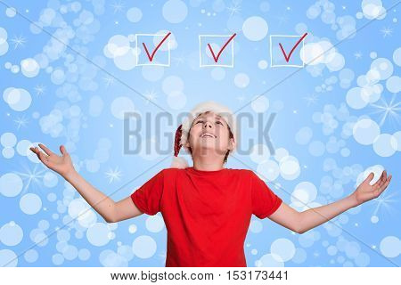 Boy in Santa hat looking upwards on holiday Christmas background. New Year resolutions or check list concept.