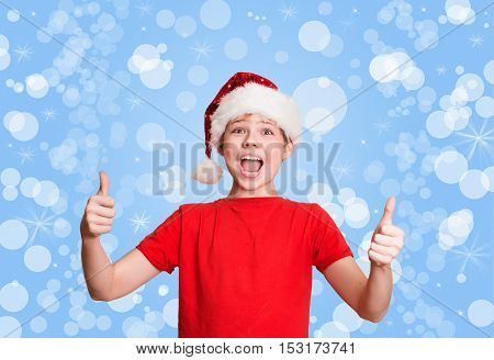 Happy preteen boy in santa hat making thumb up gesture on holiday Christmas background.