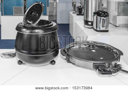 Electrical kitchen equipment electric pressure cooker and frying pan in the foreground