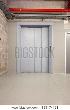 an closed elevator on the first floor of an long corridor