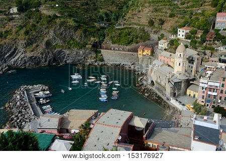 Vernazza Italy - September 4 2016: Buildings and boats in small port in Vernazza city in Liguria Italy. One of five Cinque Terre cities (unesco world heritage). Unidentified people visible.