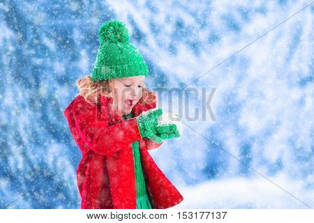 Little girl in red jacket and green knitted hat catching snowflakes in winter park on Christmas eve. Kids play outdoor in snowy winter forest. Children catch snow flakes on Xmas. Toddler kid playing.