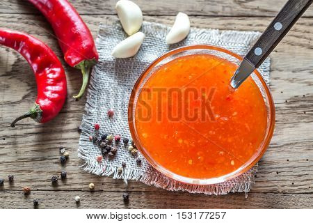 Glass bowl of thai sweet chili sauce on the wooden table