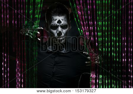 Portrait of a man with a mexican calaveras makeup looking through the curtain