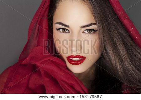 beautiful woman portrait with red lips and red veil over her head studio shot