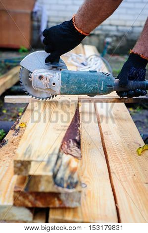 Men Use Hand Held Power Saw To Cut Planks Of Wood For Home Construction