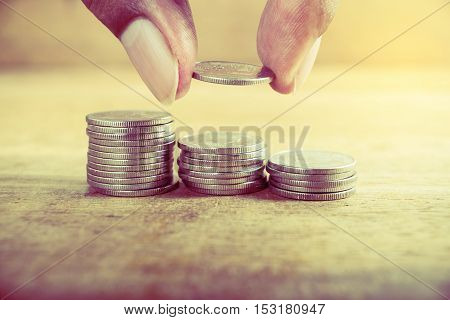 Vintage close up of hand stacking silver coins on wooden table, Save money for prepare, Save money concept