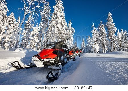 Group of red snowmobiles in Finnish Lapland sunny landscape