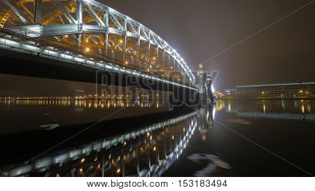Illuminated Peter the Great Bridge across Neva River in night Saint Petersburg, Russia