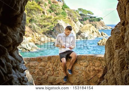 A handsome young man in the big cave view from inside. Beutiful sea and island view on the background.