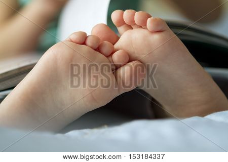 Foot closeup. An image of a toddler reading a book.