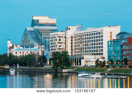 Riga, Latvia - June 30, 2016: The Evening Cityscape At The Bank Of Daugava River. Urban View Of National Library Building Lock Of Light And Contemporary Hotels At Scenic Illuminated Embankment Pier Under Blue Sky.