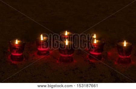 Burning votive candles in a dark room