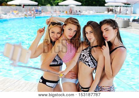 Four girl friends in bikinis with Selfie stick on the pool background