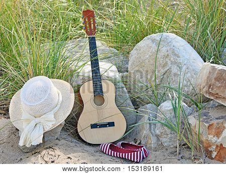 guitar leaning on beach rocks  in grass with hat and striped shoes
